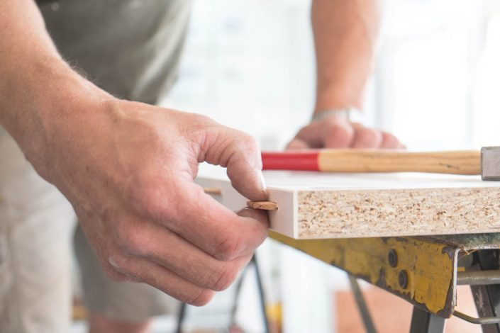 Nahaufnahme mit Hand, Hammer und Holz