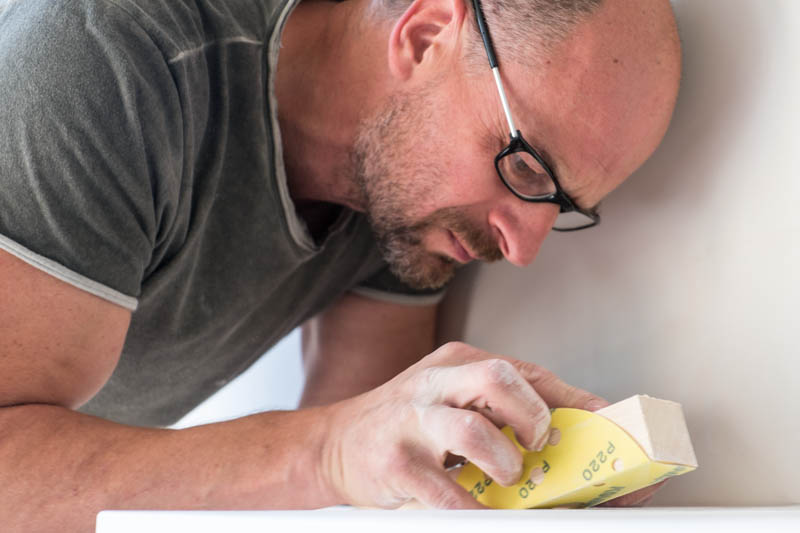 Mitarbeiter bei Schleifarbeiten mit Schmirgelpapier