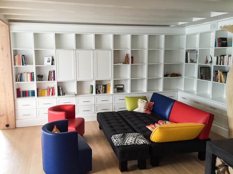 weisses deckenhohes Bücherregal mit bunten Sofa