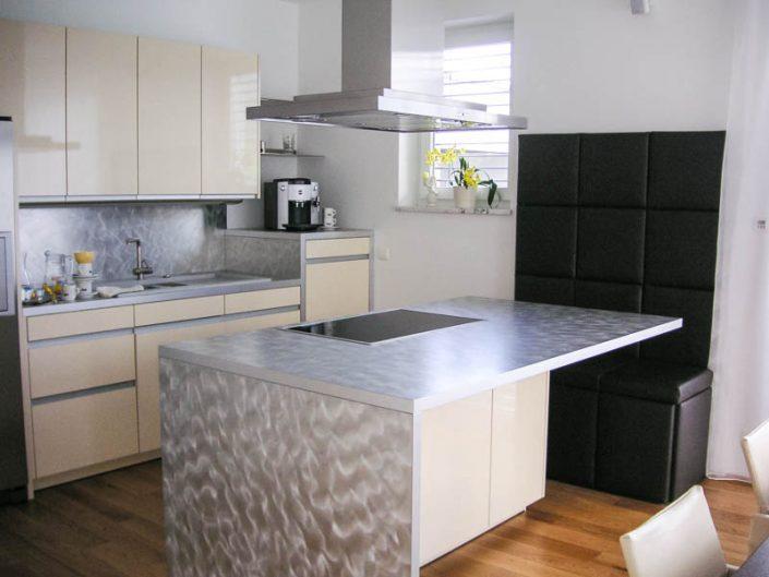 Küche mit glänzend lakierten Fronten und schwarzer Sitzbank mit Leder Arbeitsfläche Alu