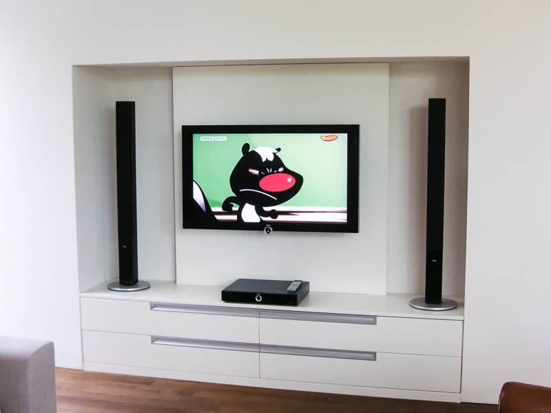 Wohnwand weiss lackiert mit schwarzem TV und scharzen Boxen
