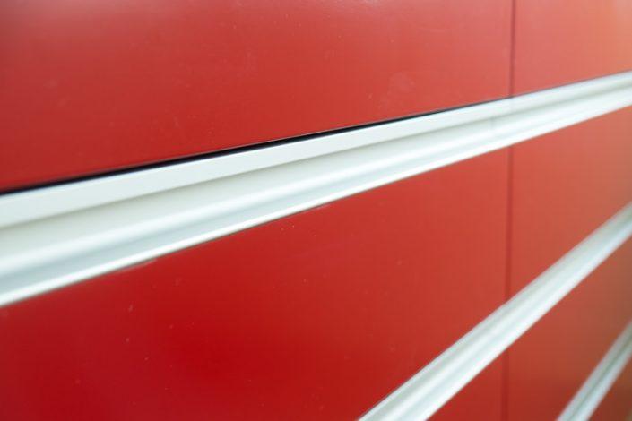 Detail Badmöbel rot lackiert mit flächenbündigen Griffleisten aus Alu